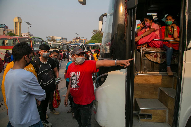 Drukte op een busstation in Kathmandu. Een dag voor de tweede lockdown ingaat, op donderdag 29 april, proberen duizenden de Nepalese hoofdstad nog te verlaten.  Beeld AP