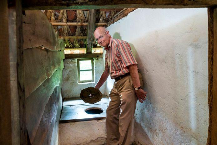 Piet Blok haalt het deksel van de pot in een Beltrumse boerderij in het Nederlands Openluchtmuseum in Arnhem.
