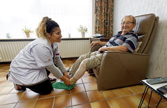 Een zorgmedewerker helpt bij het aantrekken van steunkousen. Foto ter illustratie.