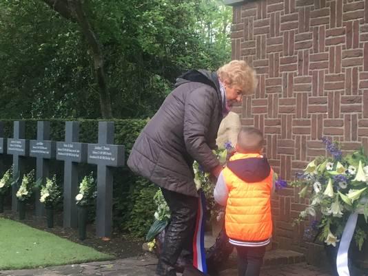 De echtgenote van een zoon van één van de verzetshelden en jonge bezoeker leggen een krans tijdens Dodenherdenking op begraafplaats Westduin in Den Haag.
