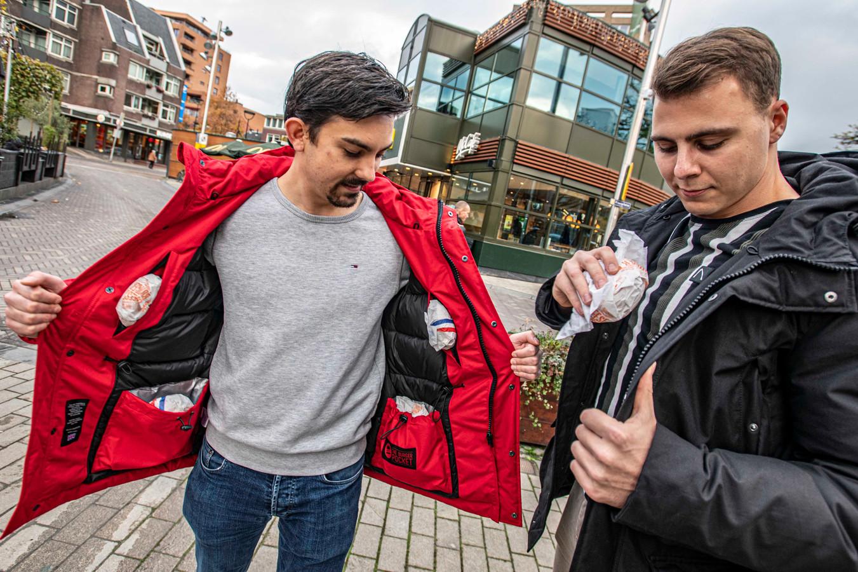 Henk Aardenhout (l) en Chris Daniëls stoppen hun jack vol met hun favoriete snack op het Piusplein.