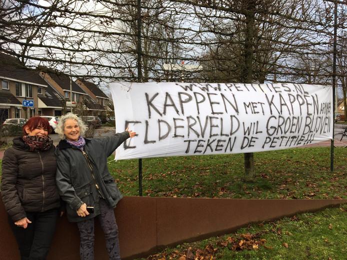Actievoerders Trudy van der Werf (l)  en Carolien van der Waarde tonen het spandoek tegen het kappen van een bosje aan de Wassenaarweg in de Arnhemse wijk Elderveld.