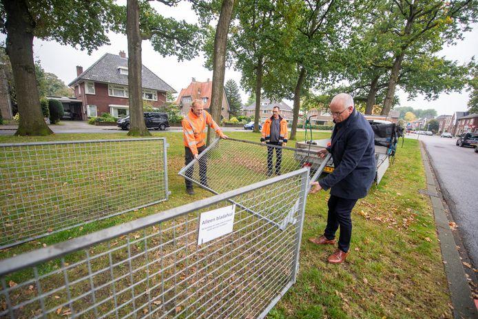 Wethouder Jan Martin van Rees helpt buitendienst medewerkers Björn Tabois (links) en Ed van den Berg (midden) bij de plaatsing van de bladkorf aan de Vissedijk.