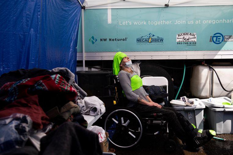 Een vrouw in een cooling center heeft koude doeken op haar hoofd en borst. Beeld The Washington Post