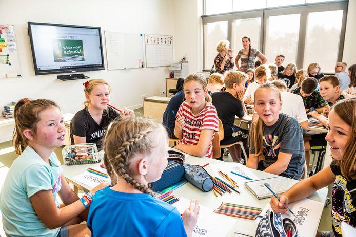 Bovenbouwers maken tijdens de eerste schooldag op basisschool De Vaart in Ter Aar hun eerste opdracht in het nieuwe klaslokaal. Van rechts met de klok mee: Maud, Maaike, Rosanna, Madelon, Eva en Lizzie.