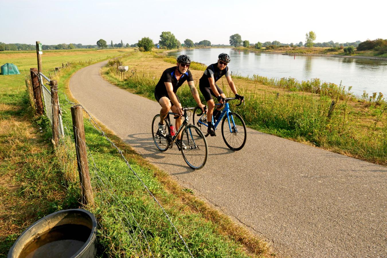 Twee fietsers op een pad aan de oever van de IJssel tussen Deventer en Zutphen. Zomer in NL, Quatre Bras.
