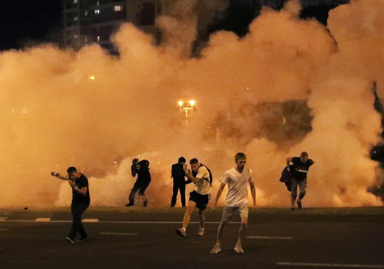 Demonstranten rennen weg van een traangasaanval in Minsk. Beeld EPA