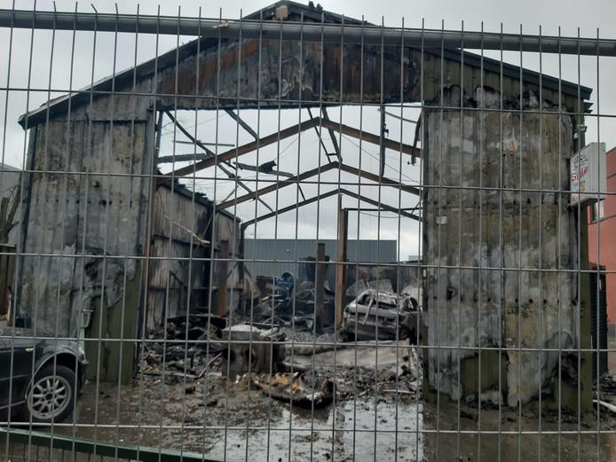 De loods van het autobedrijf in Helmond bij daglicht na de brand.