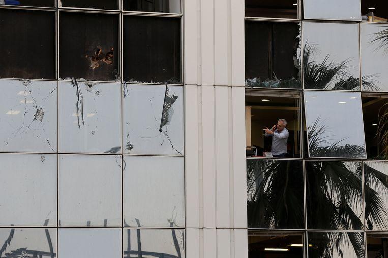 Een man bekijkt de ravage na de bomaanslag op het redactiegebouw van Skai TV. Beeld REUTERS