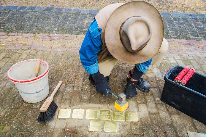 Gunter Demnig klopt de struikelstenen in de Moergestelse grond.