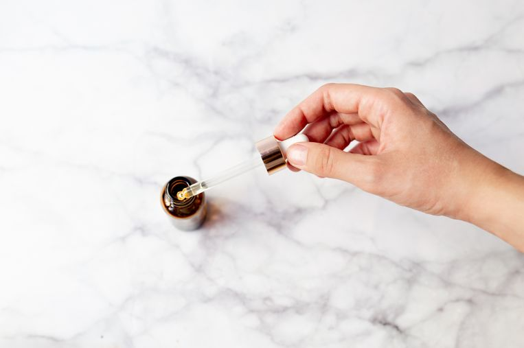 Top view of hand holding a retinol oil serum pipette and oil bottle on isolated marble background. Beauty care concept. Beeld Getty Images/500px Plus