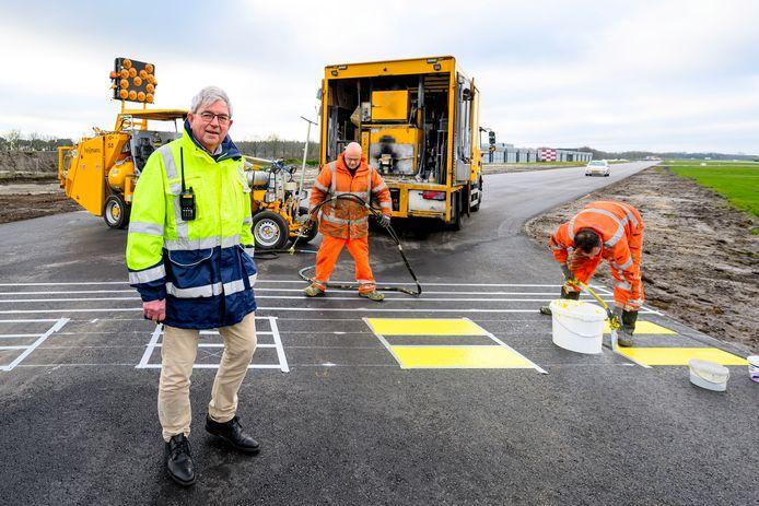 Havenmeester Jan Voeten bij de wegwerkers op Breda Airport. Het vliegveld krijgt geasfalteerde taxibanen.