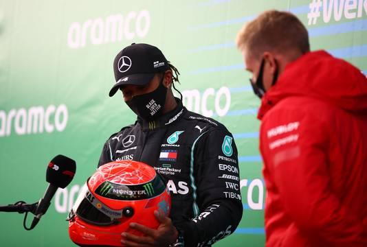 Mick Schumacher overhandigt Lewis Hamilton een speciale helm.