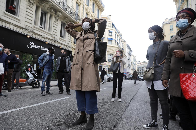 Omstanders aan de basiliek Notre-Dame de Nice reageren geschokt op de terreurdaad. Beeld EPA