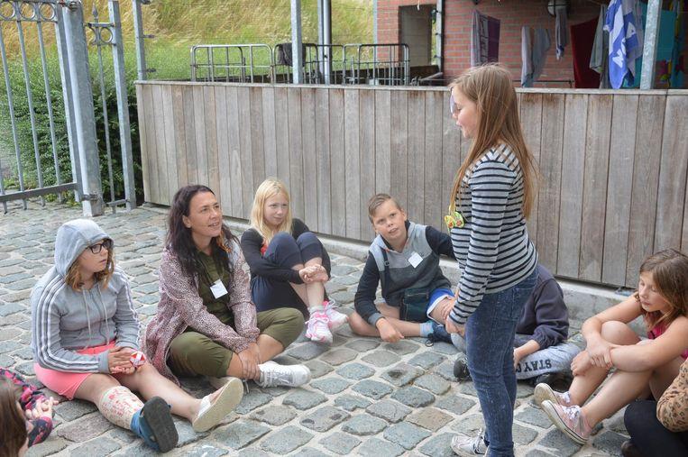 Slongs Dievanongs speelt een spel met de kinderen.