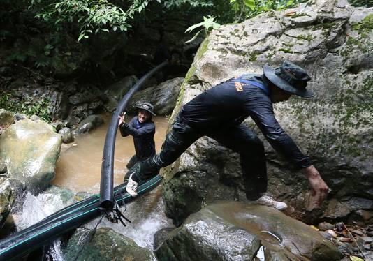 Soldaten zijn met buizen bezig om de waterloop van de beek bij de grot te verleggen