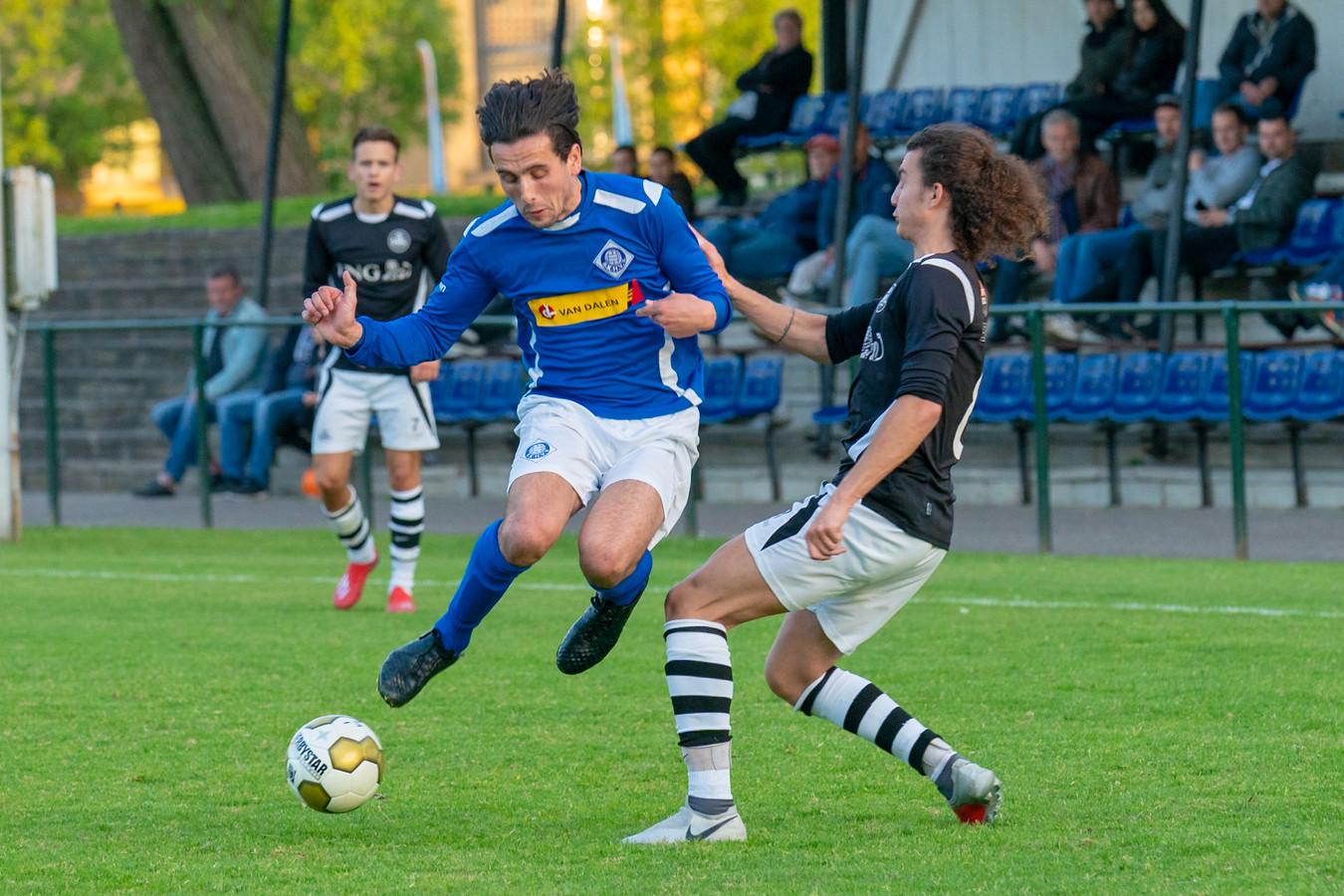 Mex Bakker, doelpuntenmaker voor RKHVV, ontwijkt een tackle van Dylan Rovroy van SML.