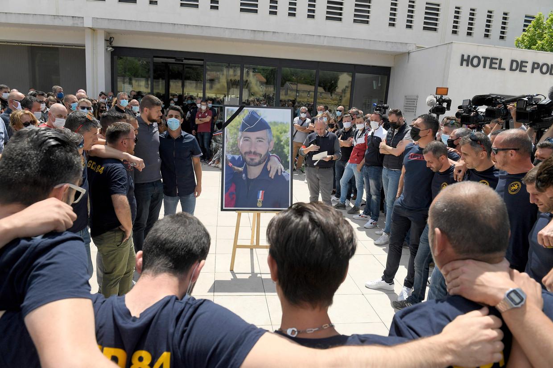 Politiemensen in Avignon staan rond het portret van de begin mei doodgeschoten collega Éric Masson.   Beeld AFP