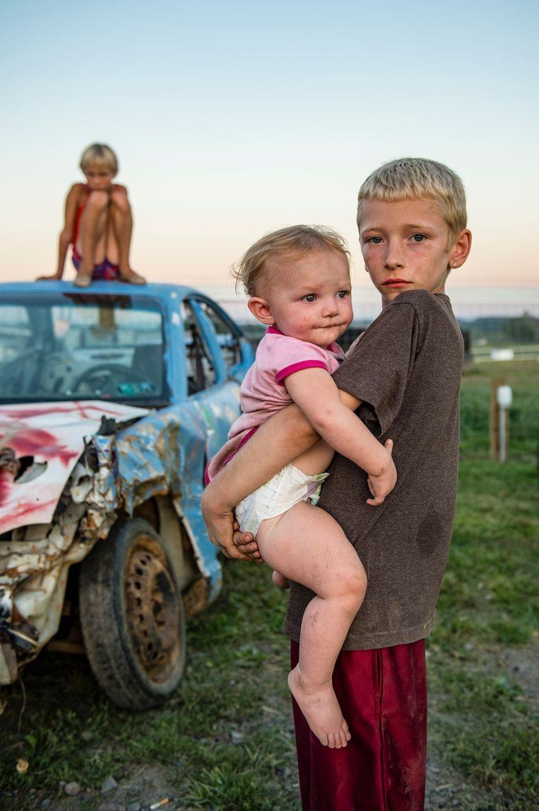 Michael Zombro (9) past op baby Alexxiz waar hij drie dollar per uur mee verdient: 'Nog drie jaar en dan mag ik ook rijden. Maar ik zou het nu al kunnen, hoor.' Beeld Cynthia van Elk