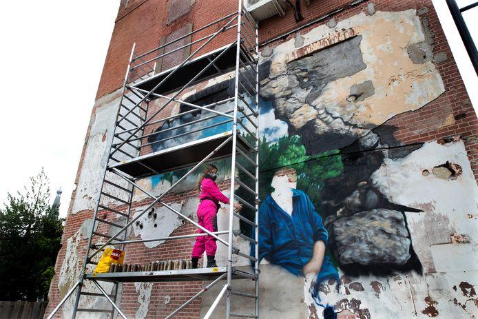 Rosalie de Graaf aan het werk met de muurschildering van boerin Anna Reintjes, ooit een begrip in Doetinchem. Foto Theo Kock
