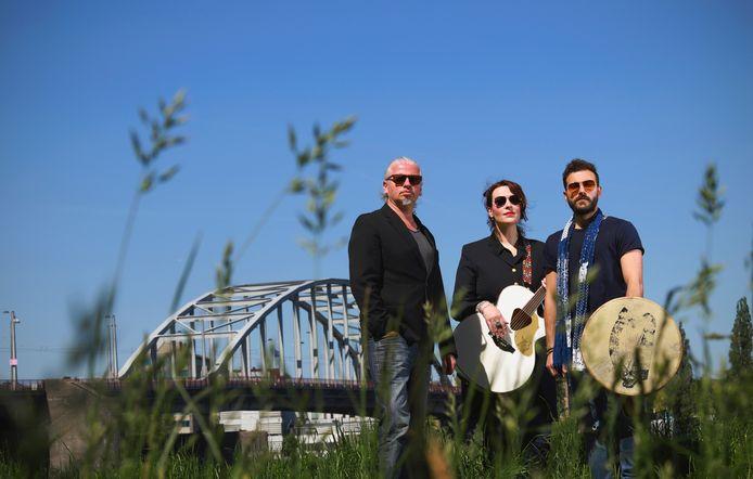 Drie mensen van de compositie 'De Brug' op de dijk bij de uiterwaarden van Malburgen in Arnhem, ter hoogte van de John Frostbrug. Vlnr: Arjan Amin, Elles Springs, Wasim Arslan.