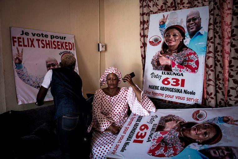 Nicole Ngebe, kandidaat bij de parlementsverkiezingen en een aanhanger van Félix Tshisekedi, voert een gesprek op haar smartphone terwijl familieleden en vrienden bij haar thuis in de weer zijn met campagneposters. Beeld AFP