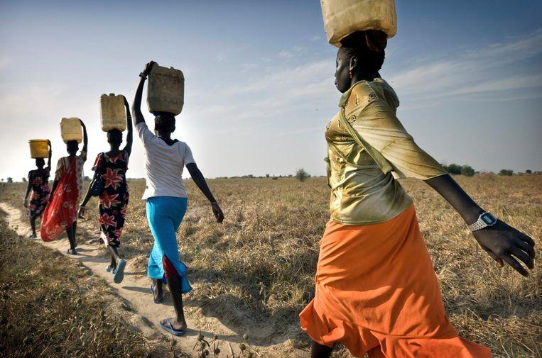 Vrouwen dragen water in een dorp in Zuid-Soedan. De inwoners zijn afhankelijk van de paar humanitaire organisaties die nog actief zijn in de regio. Veel organisaties hebben zich moeten terugtrekken door gebrek aan fondsen. Beeld null