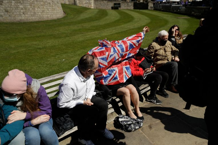 Een vrouw trekt een poncho met de Union Jack aan, terwijl mensen zich verzamelen buiten Windsor Castle. Beeld AP