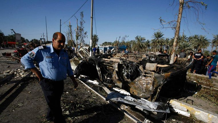 Iraakse hulpdiensten bij getroffen auto's op de controlepost in Hilla. Beeld afp