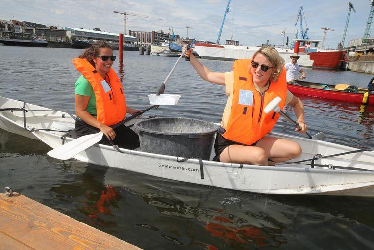 Eva (links) en Soetkin varen kano en halen daarbij vuilnis uit het water.