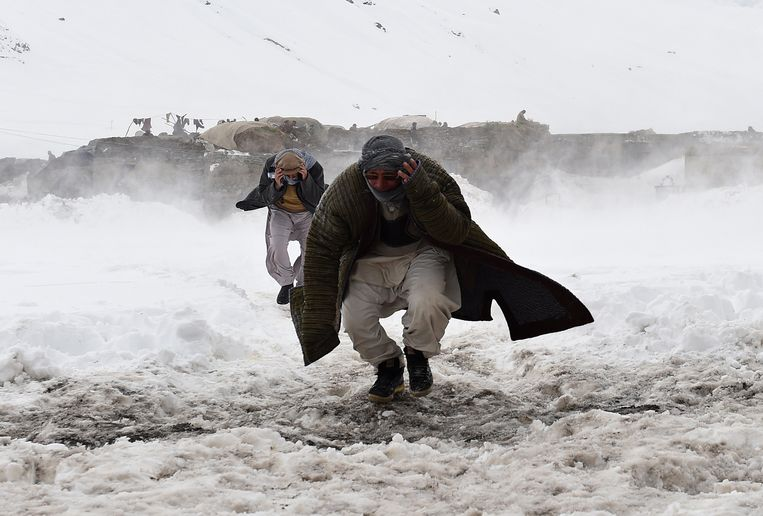 Overlevenden van een aardbeving in Panjshir rennen richting hulp van Afghaanse legerhelikopters (2015).  Beeld AFP