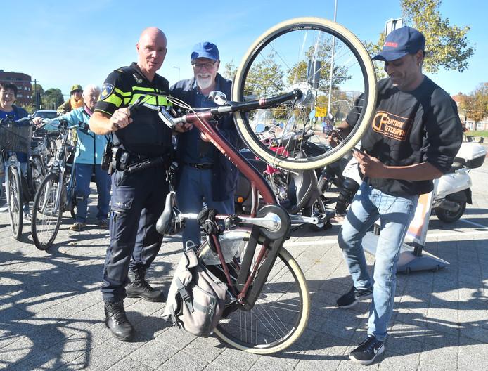 Sudish Debisarun (rechts) kijkt de fiets na van mijnheer De Vlieger.  Wijkagent Martin Vogel helpt een handje.