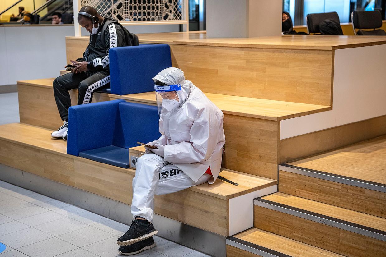 Op Schiphol doden reizigers hun tijd. Ondanks de oproep om alleen nog noodzakelijke reizen te maken, is het relatief druk op de luchthaven. Beeld Guus Dubbelman / de Volkskrant