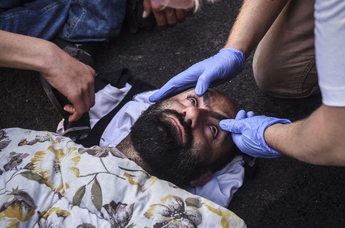 Een gewonde migrant wordt behandeld door hulpverleners.