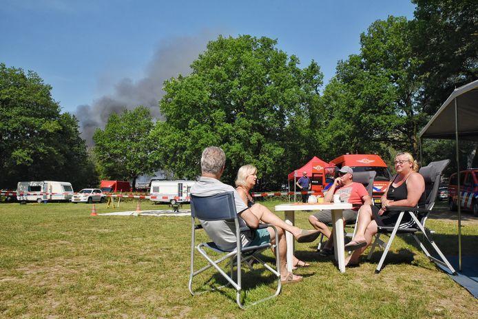Vakantiegangers Bas en Monique Verboven (links) en Jan en Linda Middelhof blijven rustig terwijl vlakbij de grote brand woedt.