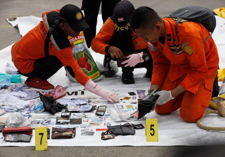 Eigendommen van omgekomen passagiers worden uitgespreid op grondzeilen.