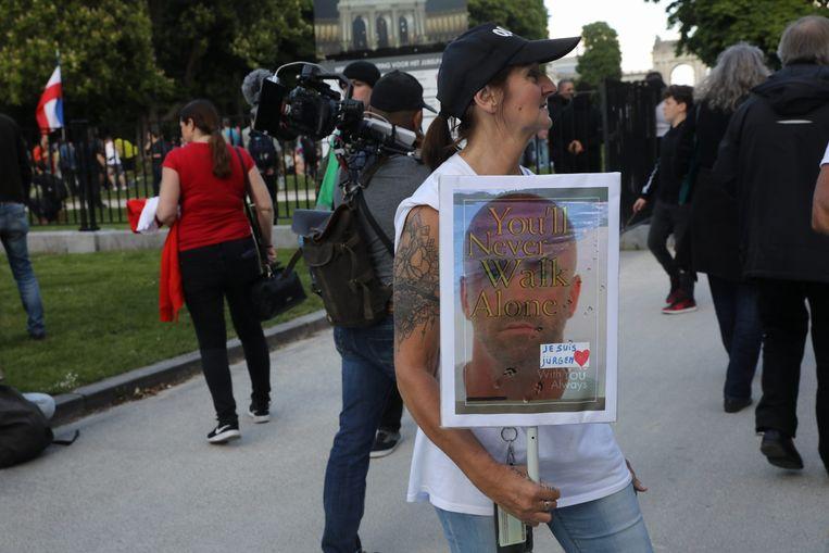 Een demonstrant in Brussel tegen de virusmaatregelen die steun betuigt aan de voortvluchtige Belgische militair.  Beeld BELGA