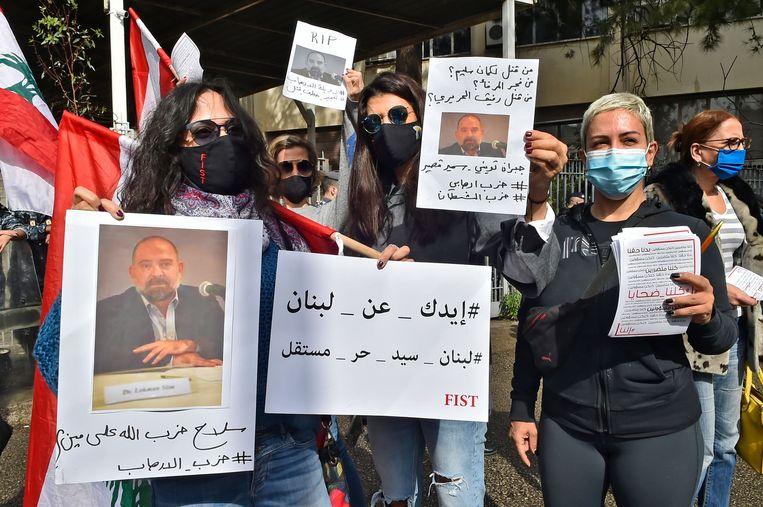 Demonstranten houden foto's omhoog van Lokman Slim bij een betoging voor het Paleis van Justitie in Beiroet op 4 februari.  Beeld AFP