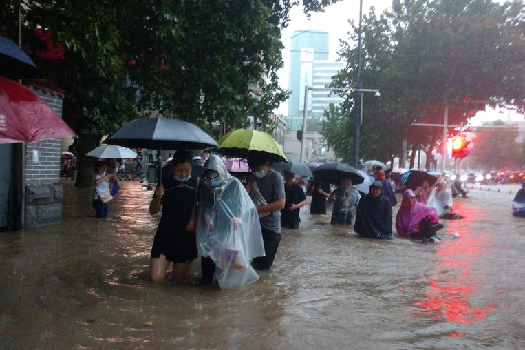 Tot hun knieën of zelfs hun middel in het water proberen mensen in de straten van de Chinese stad Zhengzhou gedurende het noodweer een veilig heenkomen te vinden. Beeld AP