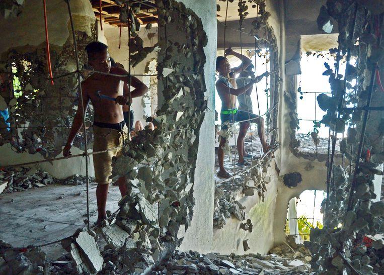 Filipijnse werkers halen de muur van een luxe-resort neer. Beeld EPA
