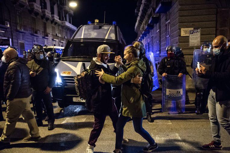 Twee demonstranten dansen tijdens protesten in Napels tegen strengere coronamaatregelen Beeld Getty Images