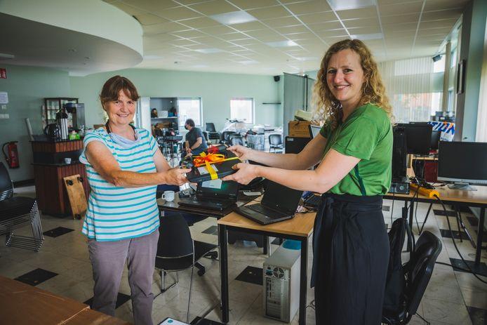 Astrid De Bruycker krijgt de 1000ste gerepareerde laptop uit handen van Karleen De Rijcke.