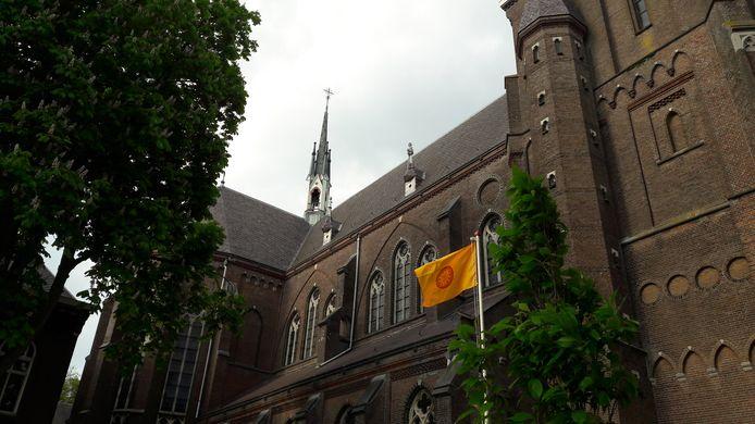 De oranje Dhammakaya-vlag wappert bij de voormalige kerk.