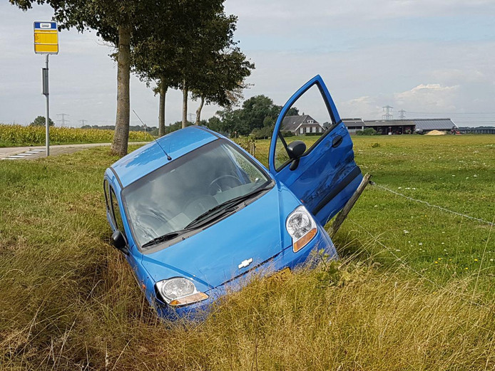 De auto in de sloot na de botsing.