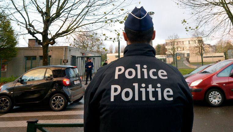 Een agent patrouilleert in de Brusselse wijk Molenbeek. Beeld Photo News