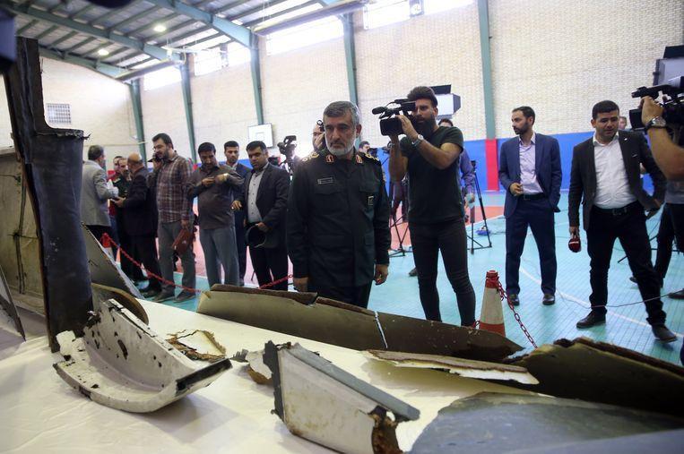 Generaal Amir Ali Hajizadeh van de Iraanse Revolutionaire Garde bekijkt brokstukken die van de Amerikaanse neergehaalde drone zouden zijn. Beeld EPA