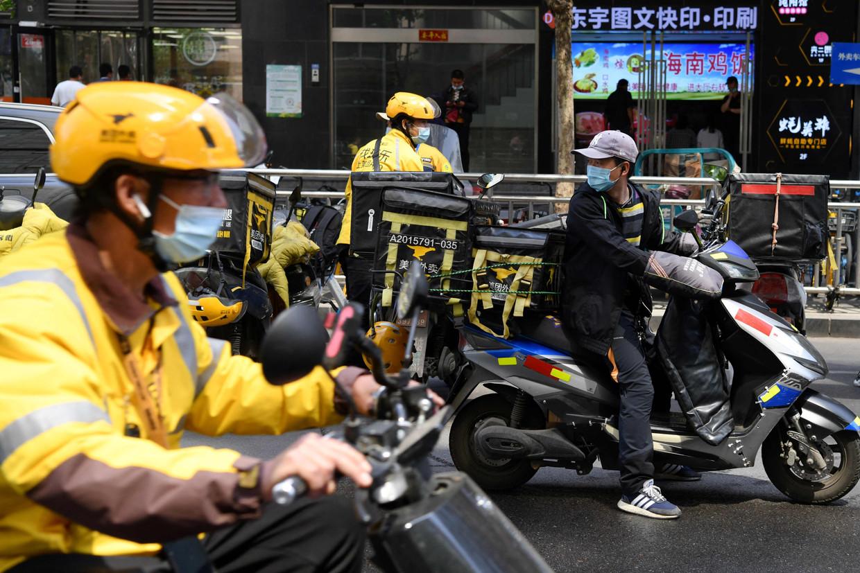Bezorgers van het bedrijf Meituan gaan op weg met maaltijden van een Pekings restaurant. Beeld AFP