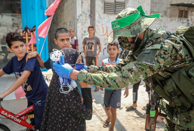 Een lid van de Ezz-Al Din Al-Qassam-brigade, de gewapende vleugel van Hamas, deelt mondmaskers uit op straat in Rafah, in het zuiden van Gaza. Beeld AFP