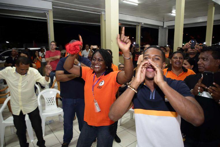 Partijleden van de VHP vieren de zetelwinst in het partijcentrum. De NDP-partij van president Desi Bouterse lijkt aan de verliezende hand te zijn bij de parlementsverkiezingen in Suriname.  Beeld ANP