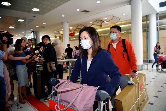 Passagiers dragen mondkapjes als ze aankomen op het internationale vliegveld van Sydney in Australië. Volgens lokale media worden reizigers gescreend door de zorgautoriteiten van het land. (23/01/2019)